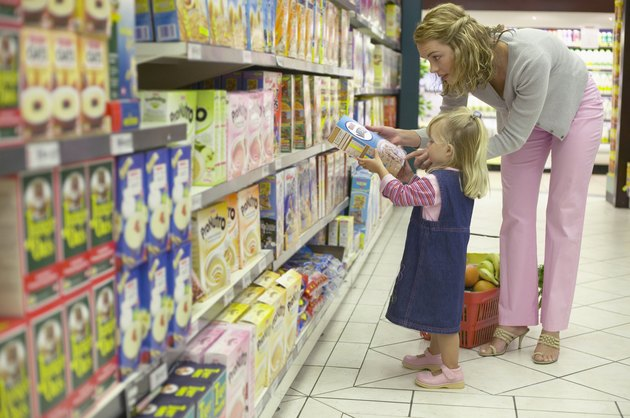 Portrait of a small girl holding a box of cereal as she shops with her mother in a grocery store