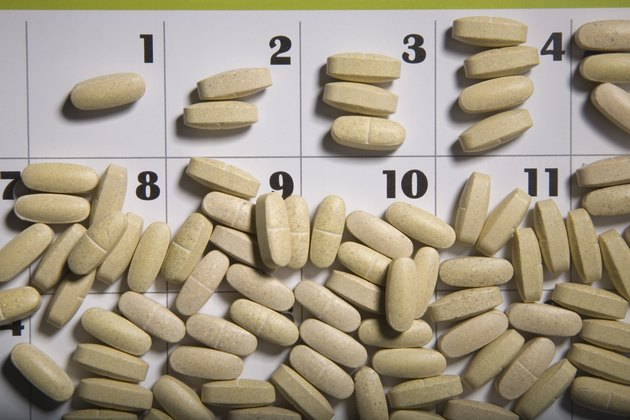 Pills scattered on a calendar page