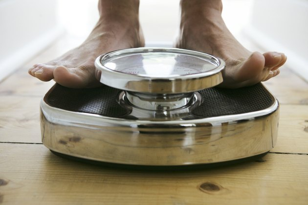 Man standing on weight scale, close-up, low section