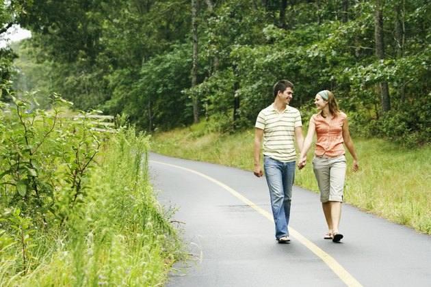 Couple holding hands while walking along path