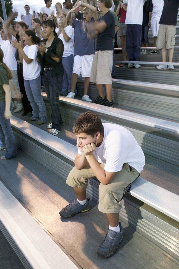 Teenage boy alone near crowd