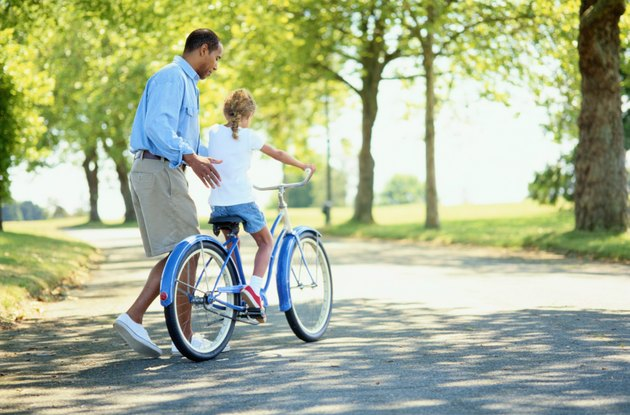 Father Helping His Daughter Ride a Bicycle