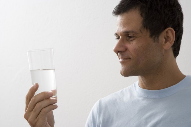 Mature man holding glass of water and smiling