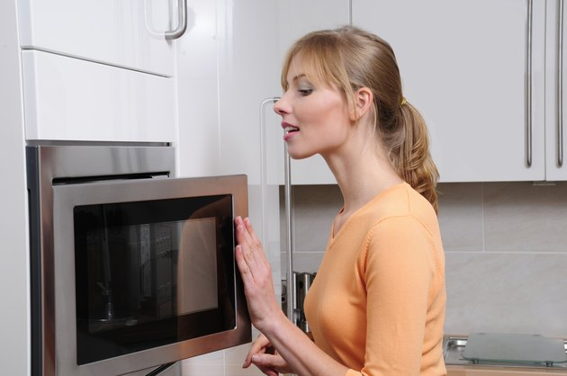 blond woman opening the microwave