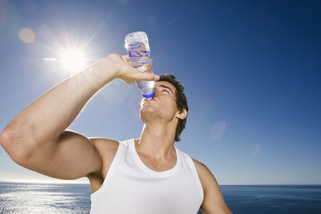 Man drinking bottle of water outdoors after workout