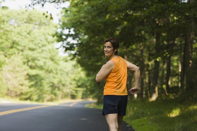 Smiling woman jogging along road