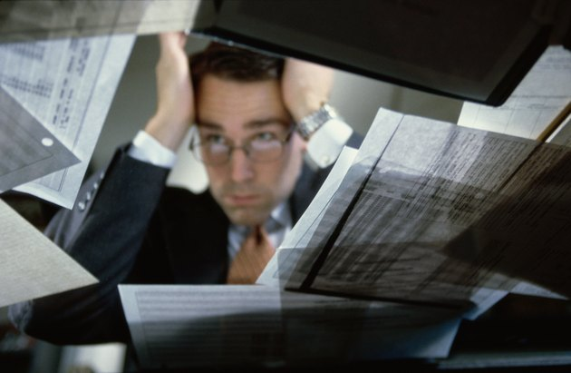 Low angle view of a businessman sitting at his desk holding his head