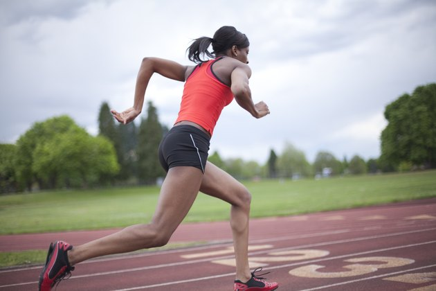 Young female sprinter accelerating, running, side view