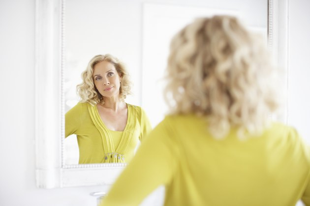 Mature woman looking in mirror