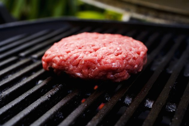 Barbecue scene, hamburger patty on the grill.