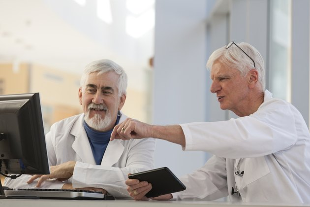 Two doctors discussing information on a computer and a tablet