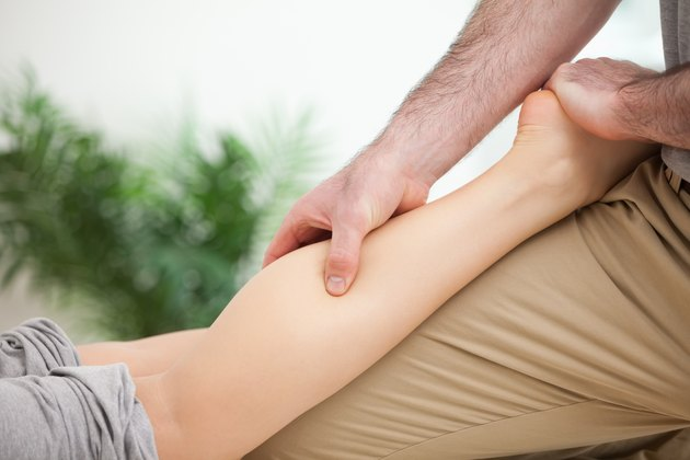Man massaging the leg of a woman while placing it on his thigh