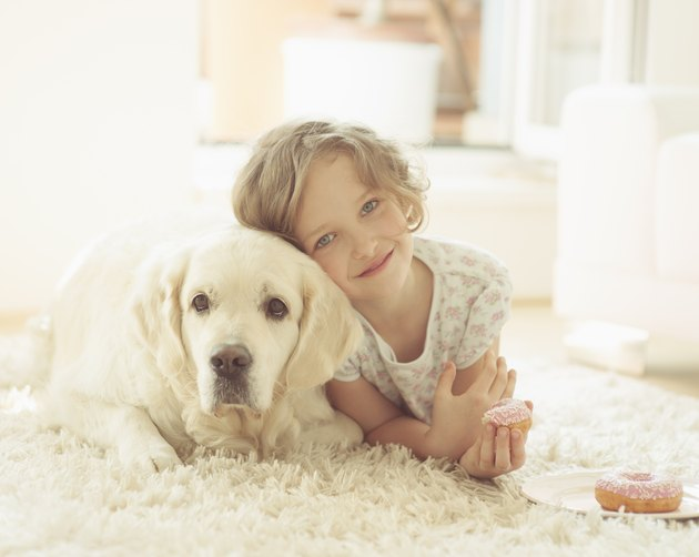 Young girl lying on rug with pet dog