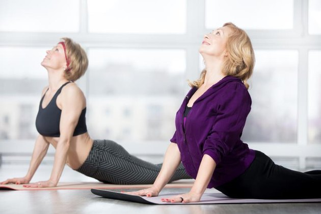 Fitness, stretching practice, group of two attractive smiling fit mature women in sportswear working out in sports club, doing Cobra posture, backbend exercise, bhudjangasana (Bhujangasana) in class