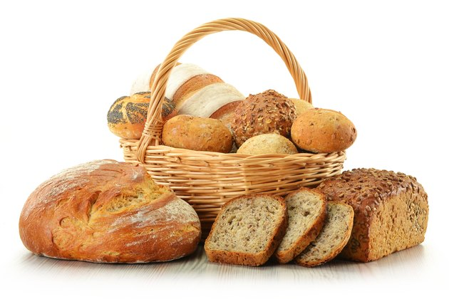 Loafs of bread and rolls in basket isolated on white
