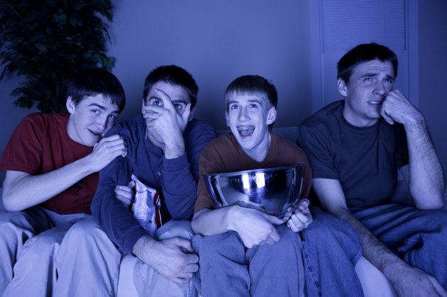 Four teenage boys (13-14) (16-17) sitting on couch watching TV, eating snacks