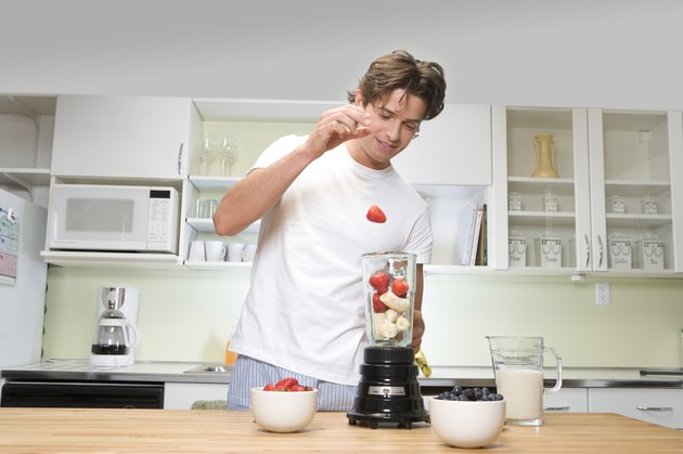Young man in kitchen, dropping strawberry into fruit filled blender