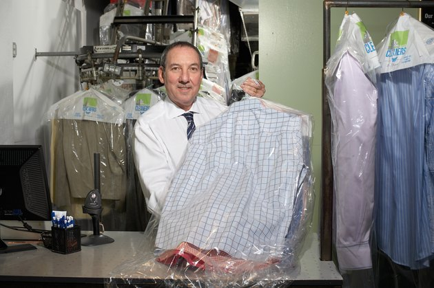 Dry cleaners operator holding shirts on hangers, portrait
