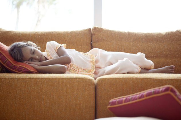 Girl (7-9) sleeping on sofa, resting head on cushion