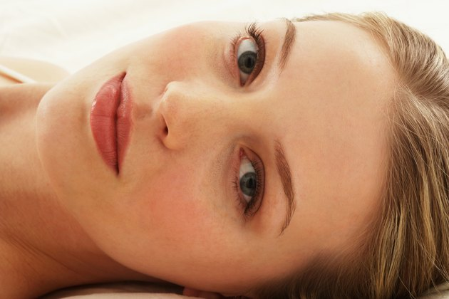 Young woman lying on bed, portrait, close-up