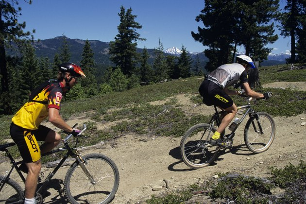Pair of mountain bikers riding up hill