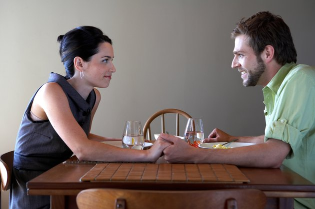 Young couple holding hands at dinner table, side view