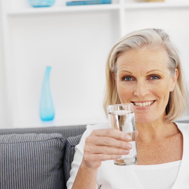 Close-up front view of mature woman holding glass of water