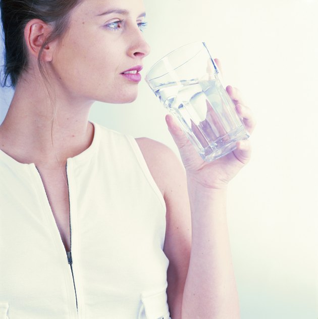 Woman holding glass of water looking away