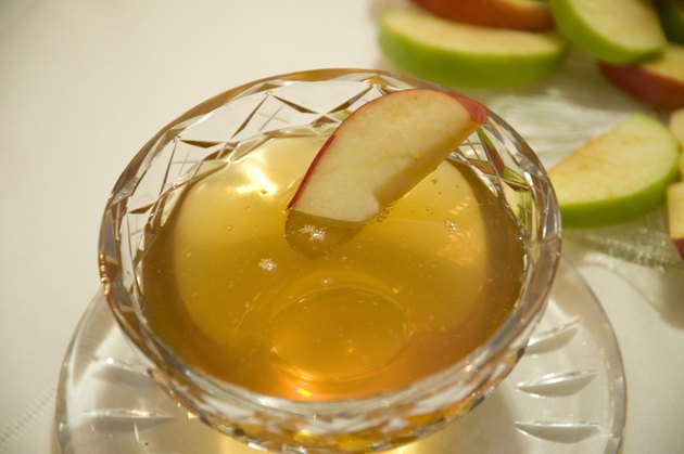 Apple slice in bowl of honey