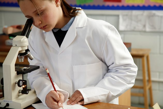 Schoolgirl (11-13) making notes while looking through microscope