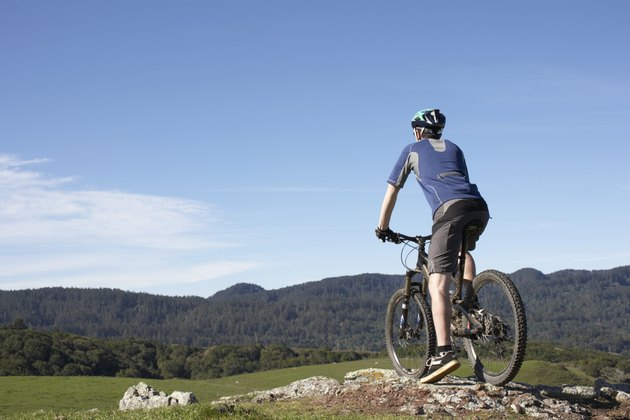 Man on mountain bike standing at edge of rock, looking at landscape, rear view