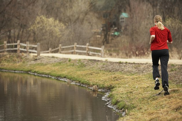 Rear view of a young woman jogging near a pond