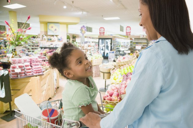 African mother and daughter shopping in grocery store