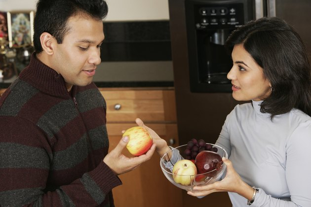 Side profile of a young woman giving apple to a young man