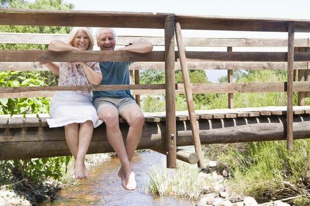 Couple sitting on rural bridge