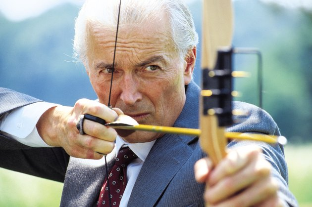 Executive archer shooting arrow