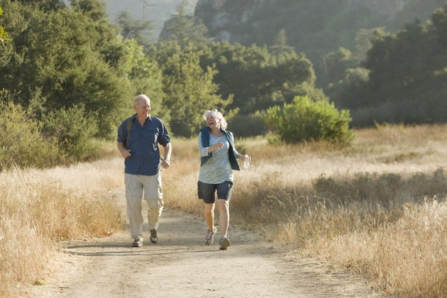 Mature couple walks down a nature trail.
