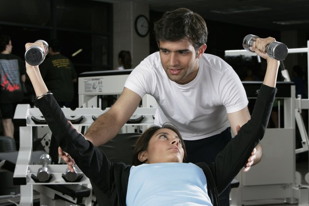 Young man teaching a young woman in a gym