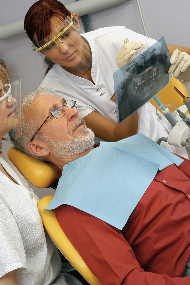 Two female dentists showing an X-Ray to a male patient