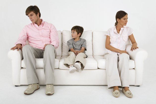 Boy sitting on couch with aloof parents