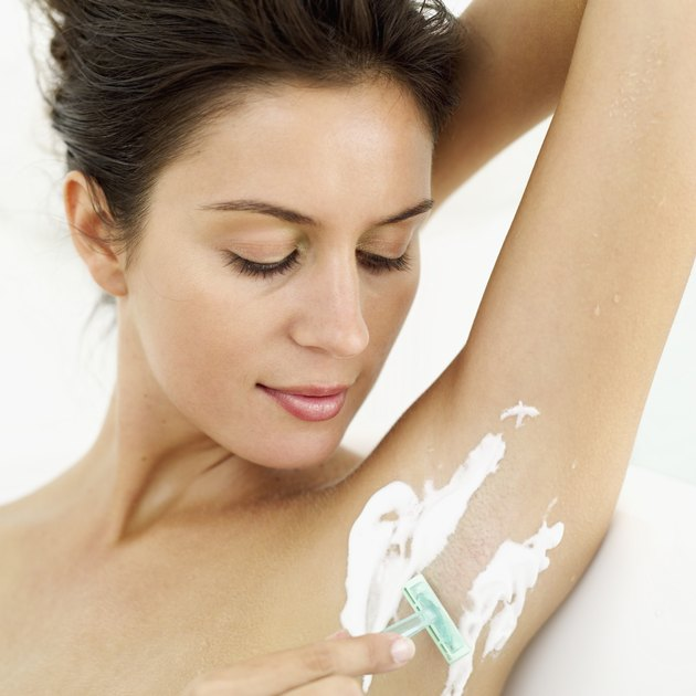 Close-up of a young woman shaving her armpits