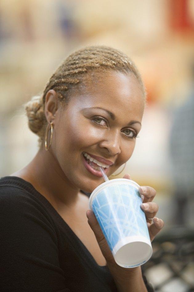 Mixed Race woman drinking fountain soda