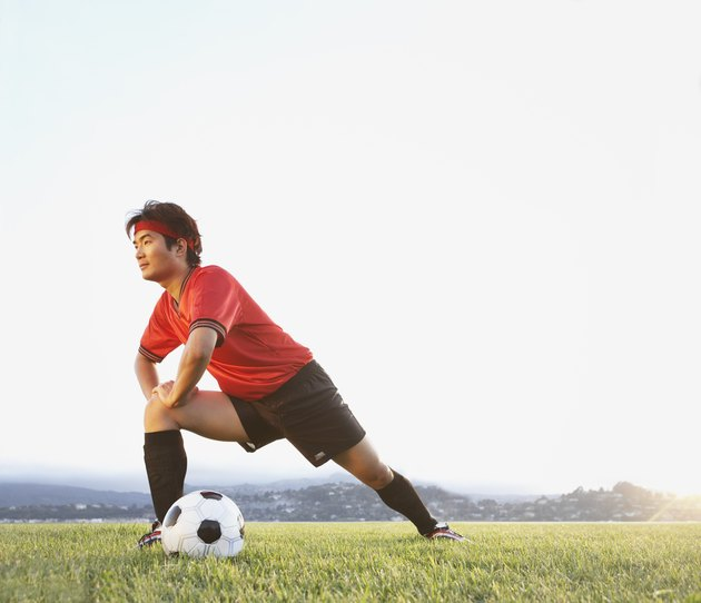 Man stretching in field with soccer ball
