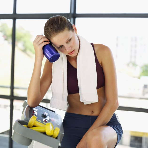 Young woman holding a bottle to her face after a workout
