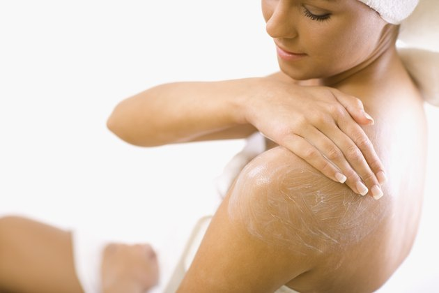 Young woman applying lotion