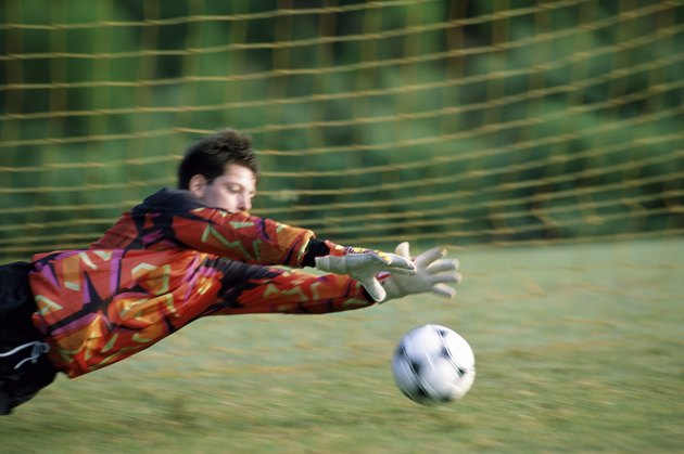 Goalie diving on a field to save the ball