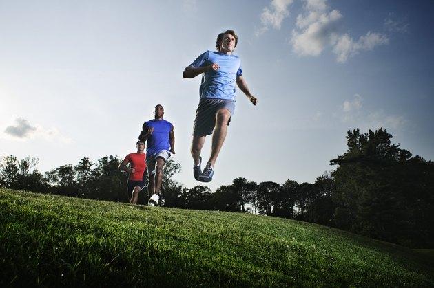 Men jumping in field