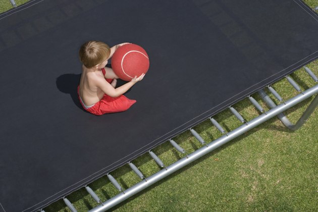 High angle view of boy with ball on trampoline