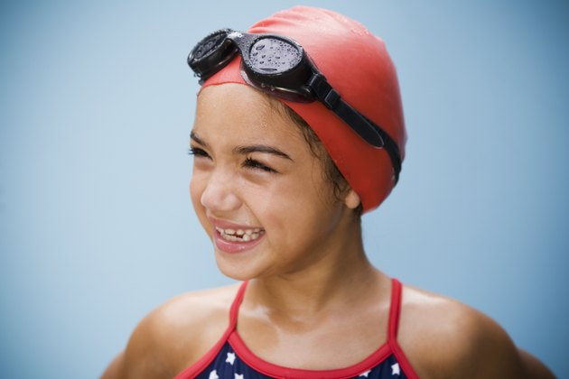 Hispanic girl in bathing suit with goggles and swim cap