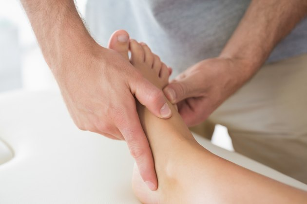 Physiotherapist massaging patients foot
